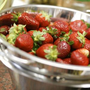 Reife Erdbeeren glänzen in einer Metallschale.