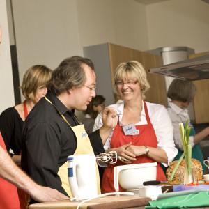 Die Teilnehmer der Cookeria Kochkurse pürrieren und mixen Soßen.