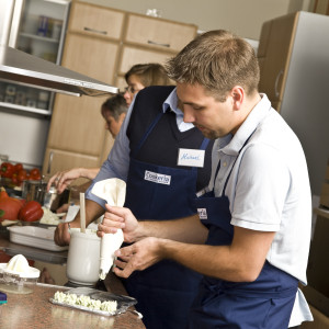 Teilnehmer der Kochkurse stellen Röschen aus Kräuterbutter her