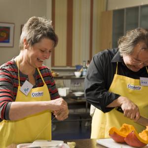 Die Teilnehmer der Kochkurse zerschneiden frische Kürbisse.